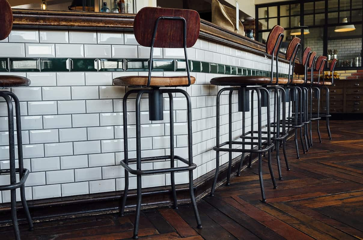 Photo of bar counter height barstools and white subway tile covered bar.